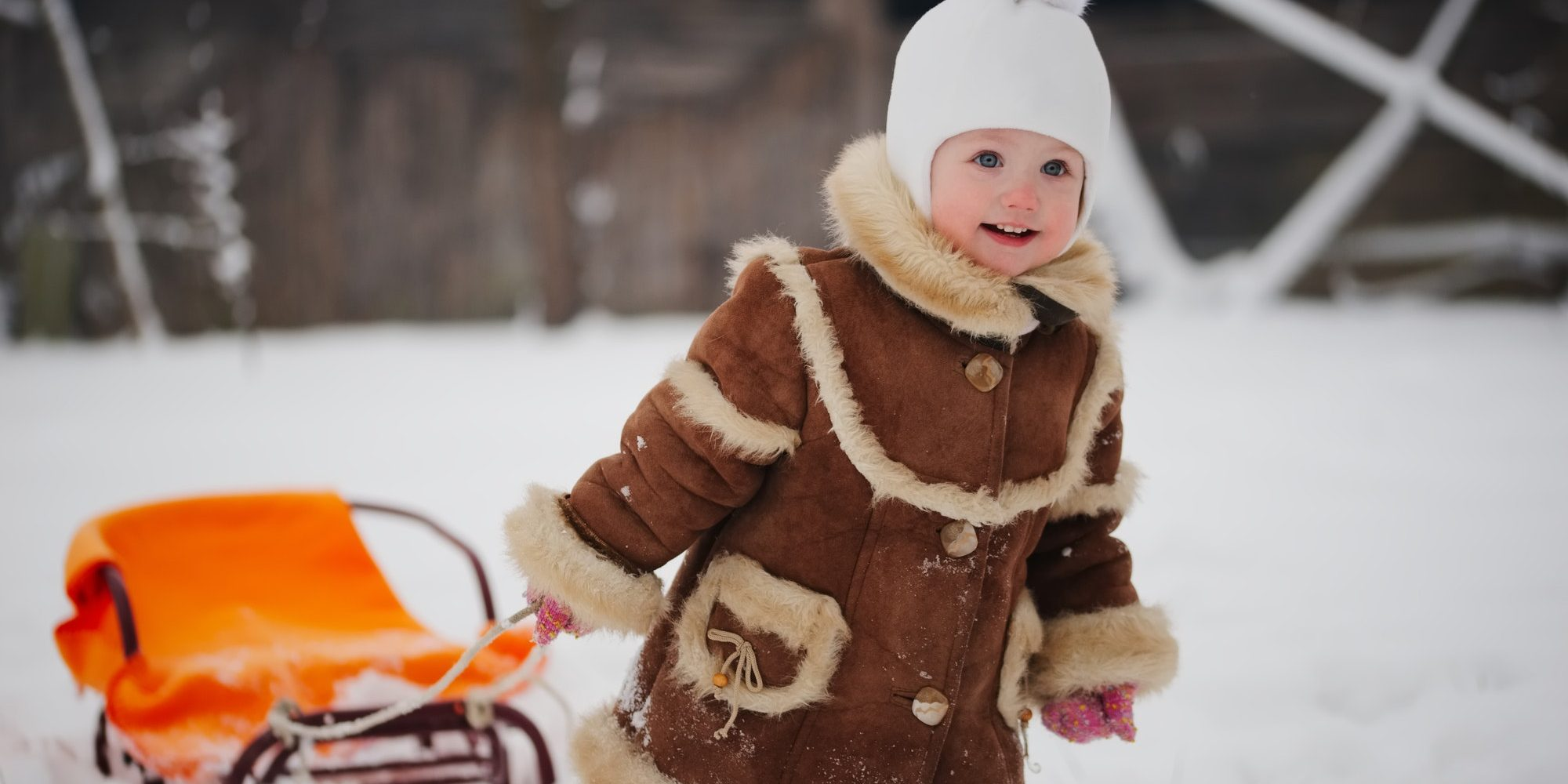cute girl with sled in snow